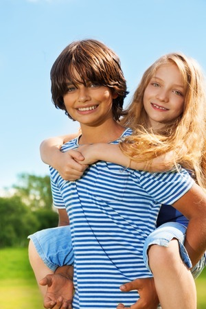 10 years old: Couple kids, boy carry girl on his back, both happy and smiling, in the park on sunny summer day Stock Photo