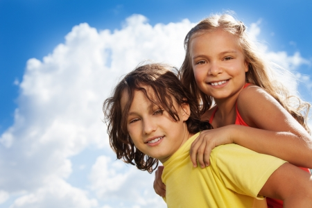 10 years old: Close portrait of two school age children boy carry girl on her back, both happy, smile, on sunny day with clouds and sky on background