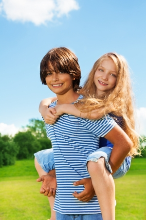 Couple beautiful kids, boy carry girl on his back, both happy and smiling, in the park on sunny summer day photo