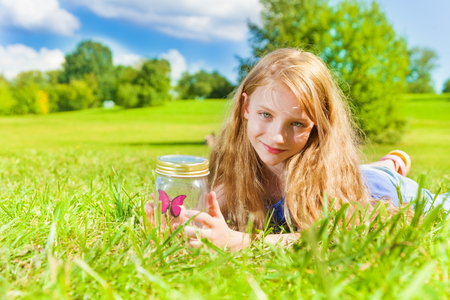 eight years old: Portrait of happy smiling girl with long dark hair 8 years laying in the grass old hold jar with butterfly standing in the park on bright sunny summer day