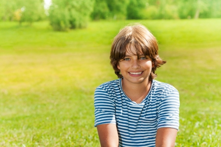 Portrait 14 yeas old boy smiling, outside on sunny day Stock Photo