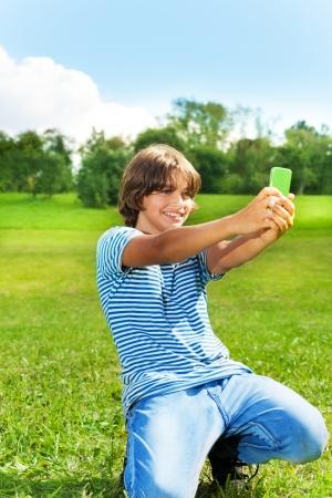 Chico de 14 años de tomar una foto de sí mismo con la cámara en el teléfono celular en el parque en el día soleado de verano