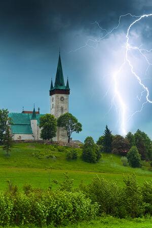 Storm with lightning in old village church in Spišský Štvrtok, Slovakia photo