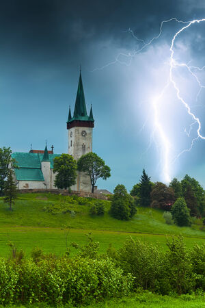 Storm with lightning in old village church in Spišský Štvrtok, Slovakia photo