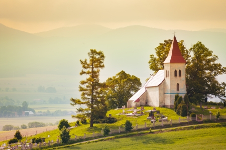 country church: Tiny beautiful small church in Slovakia village with mountain on background Stock Photo