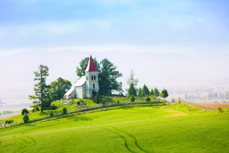church building: Slovakia rural small church in the hills and trees panorama