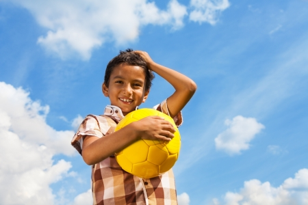 boy ball: Happy smiling boy with soccer ball holding head with hand on sky