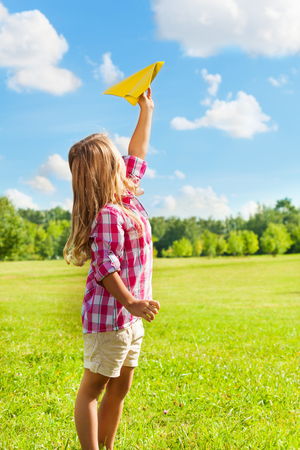 Happy blond 6 years old girl holding yellow paper airplane on bright sunny day photo