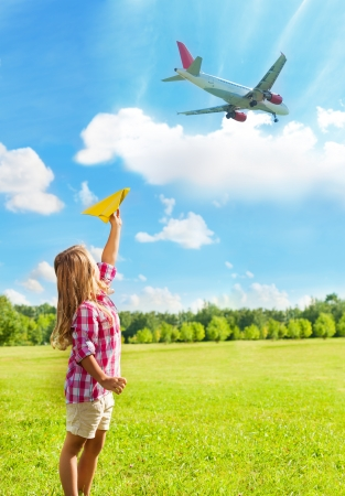 Happy little girl with yellow paper plane with real airplane on bright sunny day flying over photo