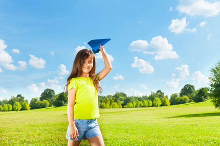 Little child holding yellow paper airplane on bright sunny day in the park photo