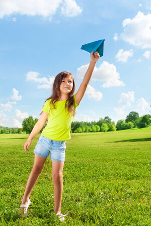 throw paper: Cute little 7 years old girl holding blue paper airplane on bright sunny day
