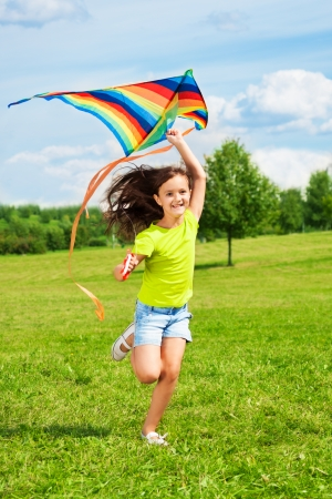 Happy little girl with kite running in the park with kite with smile and long hairs waiving on the wind photo