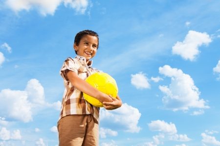 Cute little boy standing with football ball in hands over blue sky photo