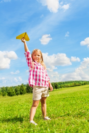 Cute little girl in pink shirt standing with yellow paper airplane on bright sunny day photo