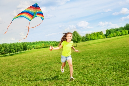 Little cute 7 years old girl running in the field with kite on summer day