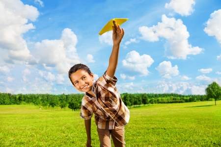 paper airplane: Happy boy leaning and throwing yellow paper airplane on bright sunny day in the field