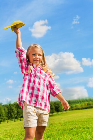 Beautiful happy girl play with yellow paper airplane on bright sunny day photo
