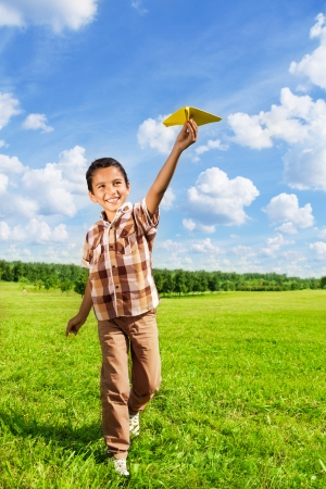 Happy boy throwing paper plane running in the park on sunny day