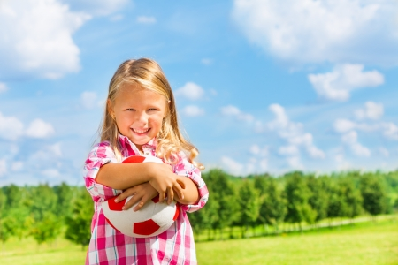 6 years: Nice little 6 years old blond cute smiling girl in pink shirt with soccer ball Stock Photo