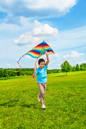 Little 6 years old boy in blue shirt running with kite in the field on summer day in the park photo