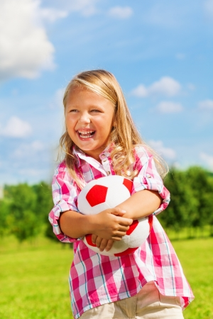 Nice little 6 years old blond cute girl in pink shirt holding soccer ball photo