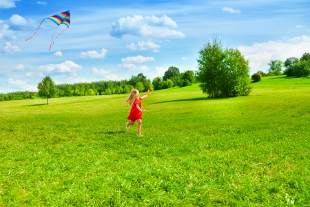 Beautiful little girl running with kite in the field on sunny summer day photo