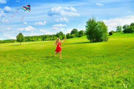 Mooi meisje lopen met vlieger in het veld op een zonnige zomerdag