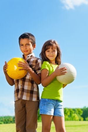child ball: Couple of kids 6 years old, boy and girl holding balls in the park Stock Photo