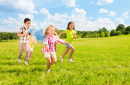 butterfly net: Kids chasing butterfly with the net, boys and girls, diversity looking, in the park on sunny summer day