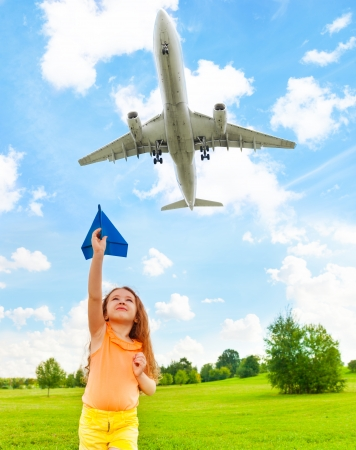 throw paper: Happy 6 years old girl holding blue paper airplane with jet flying over in the sky Stock Photo