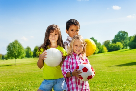 Team van drie gelukkige kinderen, jongen en meisjes die zich in het zonnige zomer park holding sportballen Stockfoto