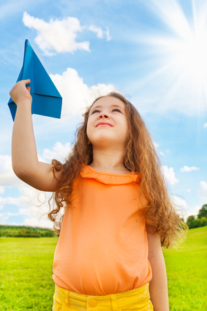 Happy 6 years old holding blue paper airplane on bright sunny day photo