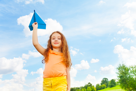 Cute happy 6 years old Caucasian girl with blue paper airplane on bright sunny day photo