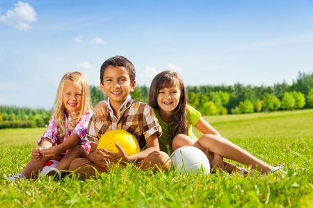 Portrait of three happy kids, boy and girls sitting in the sunny summer park holding sport balls photo