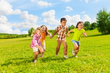 children running: Group of little 6 and 7 years old kids, boys and girls running holding hands together in the park