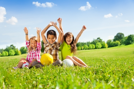 Portrait of three happy kids, boy and girls sitting in the grass in park with lifted hands and holding sport balls