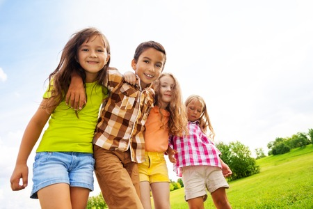 Group of hugging 6 ,7 years kids standing and hugging in the park on summer day photo