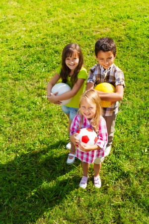 children playing together: Three happy kids, boy and girls standing in the sunny summer park holding sport balls, view from top Stock Photo