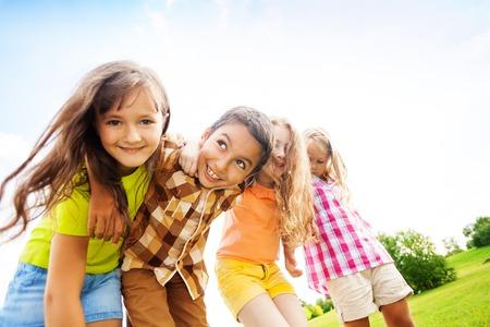 Groep kleine 6 en 7 jaar oude lachende kinderen glimlachen die buiten in het park