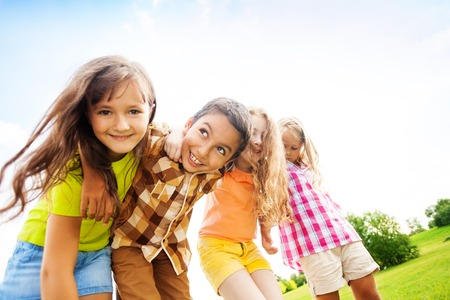 6 years girl: Group of little 6 and 7 years old smiling kids smiling standing outside in the park