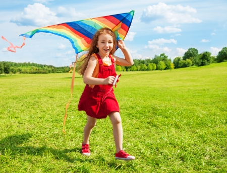 Cute little girl with long hair running holding kite in the field on summer sunny day