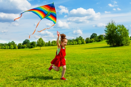 Leuk meisje met lange haren lopen met vlieger in het veld op zonnige zomerdag Stockfoto