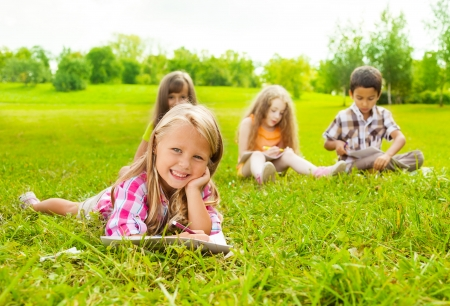 6 7: Cute little 6 years girl drawing in park outside laying on the grass with her friends