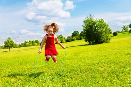 Mooie kleine 6 jaar oud meisje springen over het touw in het park op zonnige zomerdag