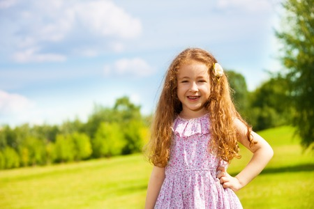 6 years: Portrait of little girl with long curly hair in the park