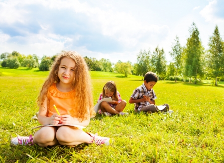 6 7: Nice little girl sitting on the grass with her friends and drawing images outside on summer day