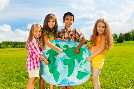6 7 years: Group of happy kids boys and girls standing and pointing to the globe map depicting diversity concept standing outside