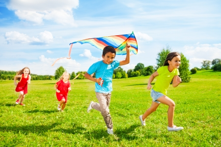 children playing outside: Group of four little kids, boy and girls running with kite in the park on summer day Stock Photo
