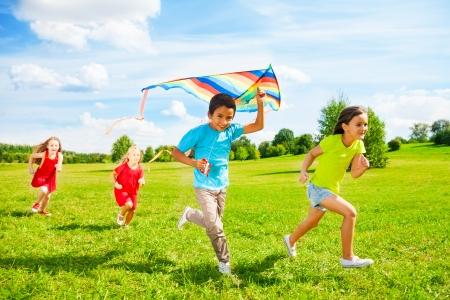 Grupo de cuatro pequeños hijos, niño y niñas corriendo con la cometa en el parque el día de verano