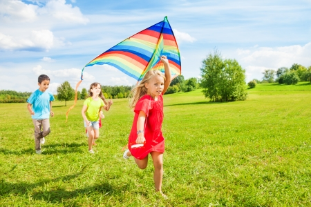 and activities: Little blond girl running in park with friends on sunny day